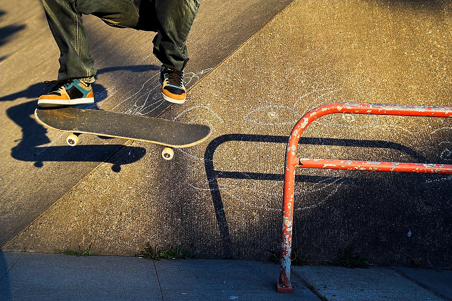 A skateboarder wearing colorful shoes jumps off a red rail outside Medgar Evers Pool in Seattle, Washington, with only the legs visible.