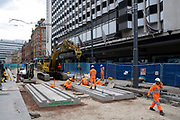 Team of workmen wearing orange high-viz overalls on a construction site work at laying the new track foundations for the update to the Midland Metro tram public transport system in the city centre along Corporation Street on 3rd August 2021 in Birmingham, United Kingdom. The original tracks are being pulled up and relaid, while a new line is also under construction and due to open later in the year. The Midland Metro is a light-rail tram line in the county of West Midlands, England, operating between the cities of Birmingham and Wolverhampton via the towns of West Bromwich and Wednesbury. The line operates on streets in urban areas, and reopened conventional rail tracks that link the towns and cities. The owners are Transport for West Midlands with operation by National Express Midland Metro, a subsidiary of National Express. TfWM itself will operate the service from October 2018.