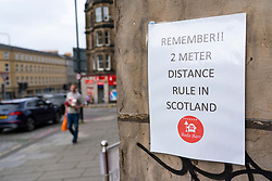 Edinburgh, Scotland, UK. 16 June, 2020. As shops open in England, Scottish shops and businesses remain closed, Streets are empty and pubs and shops are still closed with many boarded up. Bars might be allowed to open outside areas at end of week but currently they are only-permitted  to serve drinks to takeaway. Pictured; 2m social distancing sign outside pub. Iain Masterton/Alamy Live View.