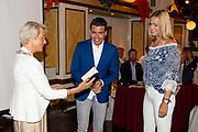 ROTTERDAM, 16-05-2020, AMVO<br /> <br /> Jan Smit heeft zijn lintje mogen ontvangen in de AMVO, Volendam.  De Volendammer wordt benoemd tot Officier in de Orde van Oranje-Nassau en is de jongste persoon die dit jaar een van de bijzondere koninklijke onderscheidingen krijgt. Jan Smit is onderscheiden voor zijn jarenlange werk als zanger, componist en presentator en vanwege zijn inzet voor verschillende goede doelen, zoals SOS Kinderdorpen, Make-A-Wish Nederland en het Oranjefonds.<br /> <br /> Op de foto:  Liza Smit Speld de versierselen op bij haar man Jan Smit