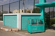 A green-painted food stall and matching background colour of a youth centre in the village of Bairat on the West Bank of Luxor, Nile Valley, Egypt. In this landscape in which nobody is seen, the lime green colours have been matched on both wall and cart.