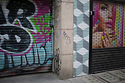 Street scene along Berwick Street with passers by interacting with graffiti and the colourful closed shutters of local shops in Soho, London, England, United Kingdom.