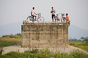Young men hang out on a collapsed bridge project across the Reu River on the southern edge of Royal Chitwan National Park, Terai, Nepal.