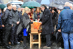 © London News Pictures. 21/03/2017. Derry, UK. Sinn Fein's Michelle O'Neill and Gerry Adams pin an Irish Flag on the coffin of Martin McGuinness before being carried though the streets the Bogside area of Derry, Northern Ireland, 21 March 2017. Sinn Féin's Martin McGuinness, Northern Ireland's former deputy first minister died aged 66 early this morning. It is understood he had been suffering from a rare heart condition. The former IRA leader turned peacemaker worked at the heart of the power-sharing government following the 1998 Good Friday Agreement. He became deputy first minister in 2007, standing alongside Democratic Unionist Party leaders Ian Paisley, Peter Robinson and Arlene Foster.. Photo credit: LNP