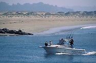 People on bow front of recreational fishing boat passing sandy beach returning to Morro Bay, California Coast