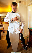 A groomsman irons out a wrinkle not wanting to have to retie his bowtie before a wedding in Napa, CA.