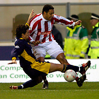 Photo: Richard Lane.<br /> Wimbledon v Stoke City. FA Cup 5th Round. 03/01/2004.<br /> Carl Asaba is tackled by Rob Gier.