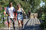 """People enjoy walking over the """"Friends Bridge"""" of the River Lea in East London as the hot weather hit Britain on Friday, Aug 7, 2020, as the UK could see record-breaking temperatures with forecasters predicting Friday as the hottest day of the year. (VXP Photo/ Vudi Xhymshiti)"""