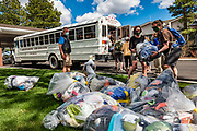 Unload the Arizona Raft Adventures (AZRA) bus in Flagstaff, Arizona after 16 days rafting 226 miles down the Colorado River in Grand Canyon National Park, Arizona, USA. During this pandemic trip (April 3-18, 2021), masks were required during the initial meeting in Flagstaff, for bus rides, for initial embarkation at Lees Ferry, for serving lines at all meals, and for final disembarkation at Diamond Creek. Otherwise, our healthy outdoor raft trip was unencumbered by facial coverings. For this photo's licensing options, please inquire at PhotoSeek.com. .