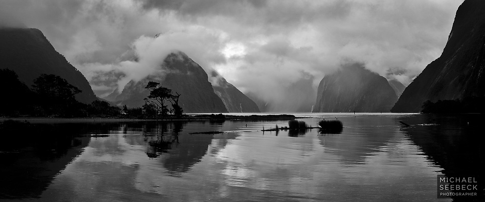 A panoramic monochrome photograph of lifting clouds over Milford Sound.<br /> <br /> Code: CZSM0001