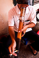 A man smokes a tobacco pipe at a drink-stall in Hanoi, Vietnam