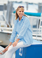 Photograph of a photo model sitting on a blue box at a marina in South Florida.