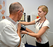 Tucson, Arizona, USA, August 16, 2014: University of Arizona College of Medicine student, Rebecca Thiede, (right), provides a free healthy eye screening for Richard Hicks, 74, as part of the UAMC Sight Savers Program.  The screening checks for cataracts, glaucoma, diabetes, macular degeneration and dry eye and is sponsored by the Department of Ophthalmology, The University of Arizona Medical Center, Alvernon Physician Offices, Tucson, Arizona, USA.