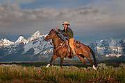 A wrangler and horse at sunrise in front of the Grand Teton mountain range in Jackson Hole, WY.