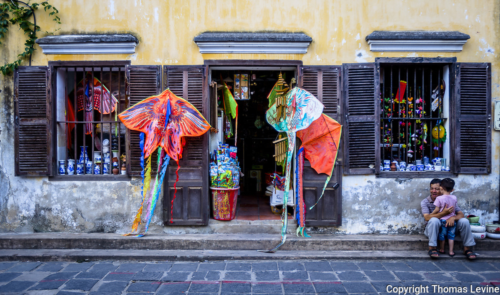 Fine Art: Aug 5, 2017, Hoi An Ancient Town, VN. <br /> Ancient building is the setting with a father and son having a comforting moment in Anicent Town Hoi An. RAW to Jpg