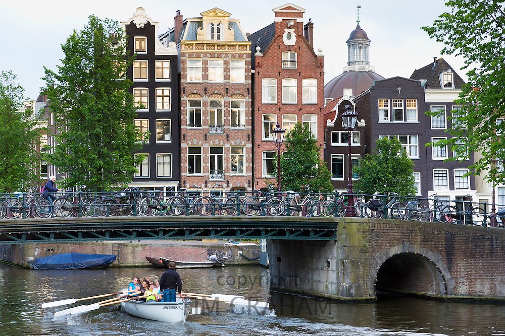 Rowing boat passes traditional Dutch architecture of canalside buildings in Prinsengracht, Amsterdam, Holland