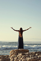 Woman by the sea with her hands in an uplifted yoga mudra.