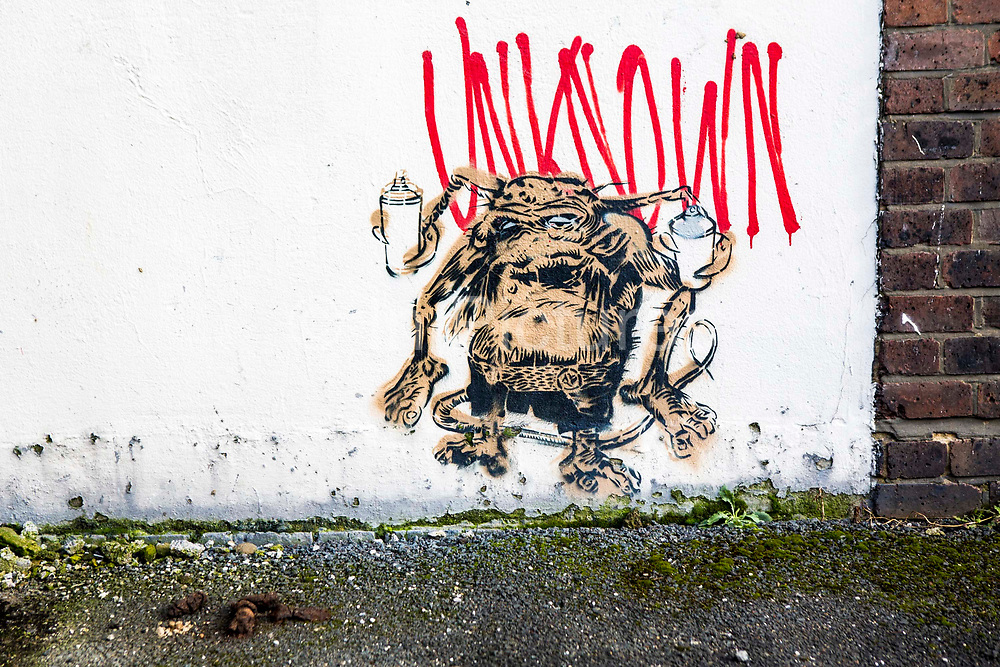 Graffiti wall art in Dalston, Hackney, London, United Kingdom. The picture is of a small gremlin or monster holding two spray paint cans.  The street art has been signed Unknown which is the artist's tag name.