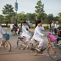 Students bike past a cement factory near the site of the of the 85th Evacuation Hospital in Phu Bai used during the Vietnam War, just outside of Hue, Vietnam.