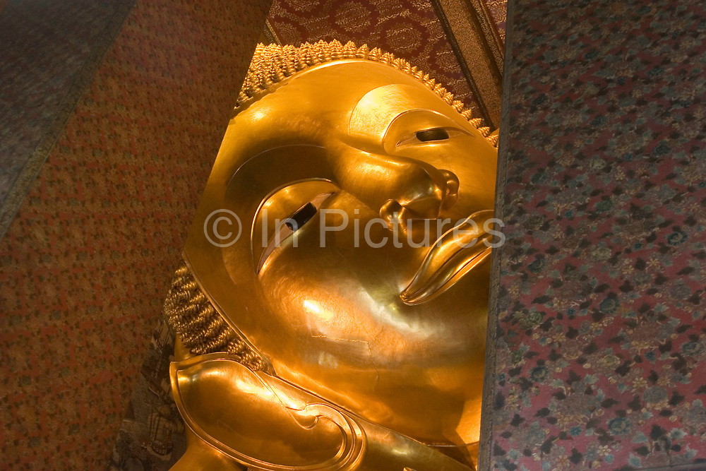The giant 45m long gold reclining Buddha at Wat Pho. This beautifully crafted Buddha has a smile 5m wide, this beaming smile because the depiction is of Buddha entering Nirvana. The black feet are beautifully inlaid with mother of pearl. Wat Pho is Bangkok's oldest temple, built in the 18th century