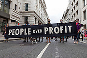 A group of climate activists from Extinction Rebellion march through the streets holding a banner that reads people for profit on 27th August, 2021 in London, United Kingdom. The activist group Extinction Rebellion XR are planning actions of disruption for two weeks straight beginning on August 23rd, 2021 in an effort to bring awareness and priority to the global climate emergency in advance of the COP 26 Summit which will be held in Glasgow later this year.