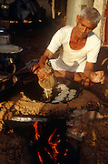 A man squeezes a mixure into a pan of boiling cooking oil to make gulab jamun sweets at the Pushkar Fair, Rajasthan, India