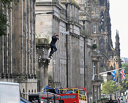 Pictured: A stuntman leaps from a building on Waterloo Place as he is showered in stage glass.<br /> <br /> <br /> Filming for the latest in the Fast and Furious franchise, 'Fast & Furious 9', continues in Edinburgh city centre.<br /> <br /> © Dave Johnston / EEm