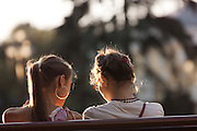 Friends talking on Moscow park bench, Aleksandrovskiy Sad, Moscow, Russia
