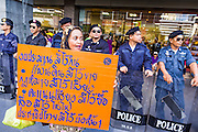 """09 JUNE 2013 - BANGKOK, THAILAND: A Thai Muslim woman who is a member of the White Masks, marches past Thai riot police during a protest against the government of Yingluck Shinawatra at Central World. The White Mask protesters wear the Guy Fawkes mask popularized by the movie """"V for Vendetta"""" and the protest groups Anonymous and Occupy. Several hundred members of the White Mask movement gathered on the plaza in front of Central World, a large shopping complex at the Ratchaprasong Intersection in Bangkok, to protest against the government of Thai Prime Minister Yingluck Shinawatra. They say that her government is corrupt and is a """"puppet"""" of ousted (and exiled) former PM Thaksin Shinawatra. Thaksin is Yingluck's brother. She was elected in 2011 when her brother endorsed her.     PHOTO BY JACK KURTZ"""