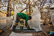 Un membre de l'équipe TANGO prépare son lit de fortune dans la réserve naturelle de Chinko. Les TANGO, dont le travail est d'aller à la rencontre des éleveurs nomades pénétrant dans la réserve avec des boeufs, passent parfois plusieurs mois en brousse.