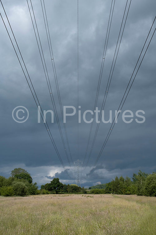 Electricity pylons along power lines under heavy grey sky in the countryside on 20th June 2020 in Studley, United Kingdom. An overhead power line is a structure used in electric power transmission and distribution to transmit electrical energy across large distances. It consists of one or more uninsulated electrical cables commonly multiples of three for three-phase power suspended by towers or poles.