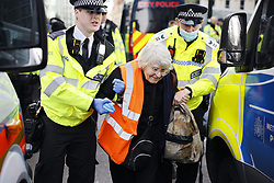 © Licensed to London News Pictures. 25/10/2021. London, UK. Police detain an elderly Insulate Britain activist at Bishopsgate in the City of London. The group have restarted their actions to block motorways and major roads causing disruption in the week before the COP26 climate meeting in Glasgow on 31/10/2021. Photo credit: Peter Macdiarmid/LNP