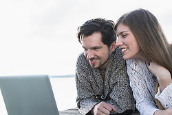 Young couple working laptop computer outdoors