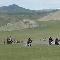 Spectators on motorcyles lead children racing bareback on 20km horse race at a naadam festival on a remote pass near Muren, Mongolia.