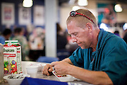 """Sept. 27 - PHOENIX, AZ: DAVID, a regular client at the Society of St. Vincent de Paul eats his lunch Monday, Sept. 27. He's been a client of their lunch service for about three years. September 27, 2010 is the 350th Feast Day of Saint Vincent de Paul, also known as the """"Apostle of Charity."""" To mark the day, the Society of St. Vincent de Paul in Phoenix served birthday cake during the lunch service. The US Census office recently announced that poverty in the US has spiked to 14.3% of the population, the highest poverty rate since 1994. Officials at St. Vincent de Paul in Phoenix said that demand for their services have increased steadily in the last three years. They currently feed about 1,100 people, either homeless or members of the working poor, every day.    Photo by Jack Kurtz"""