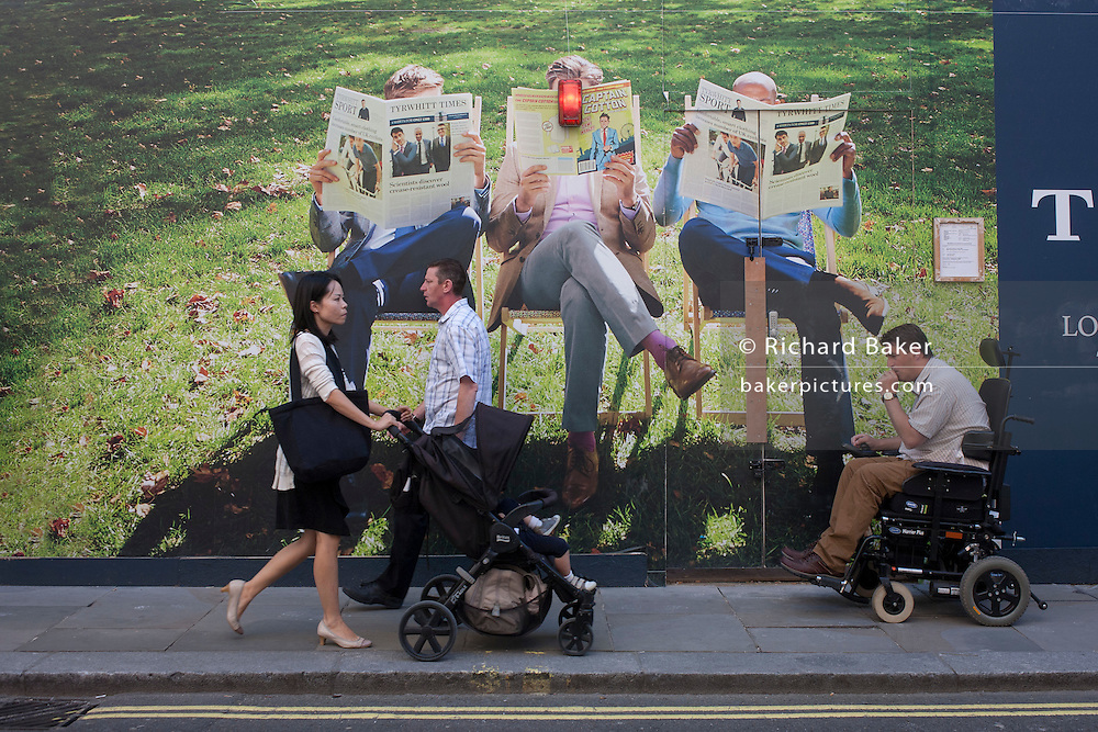 A disabled man in a wheelchair and a mother pushing a child's buggy, pass beneath a construction hoarding for fashion brand Charles Tyrwhitt, in Jermyn Street, central London.