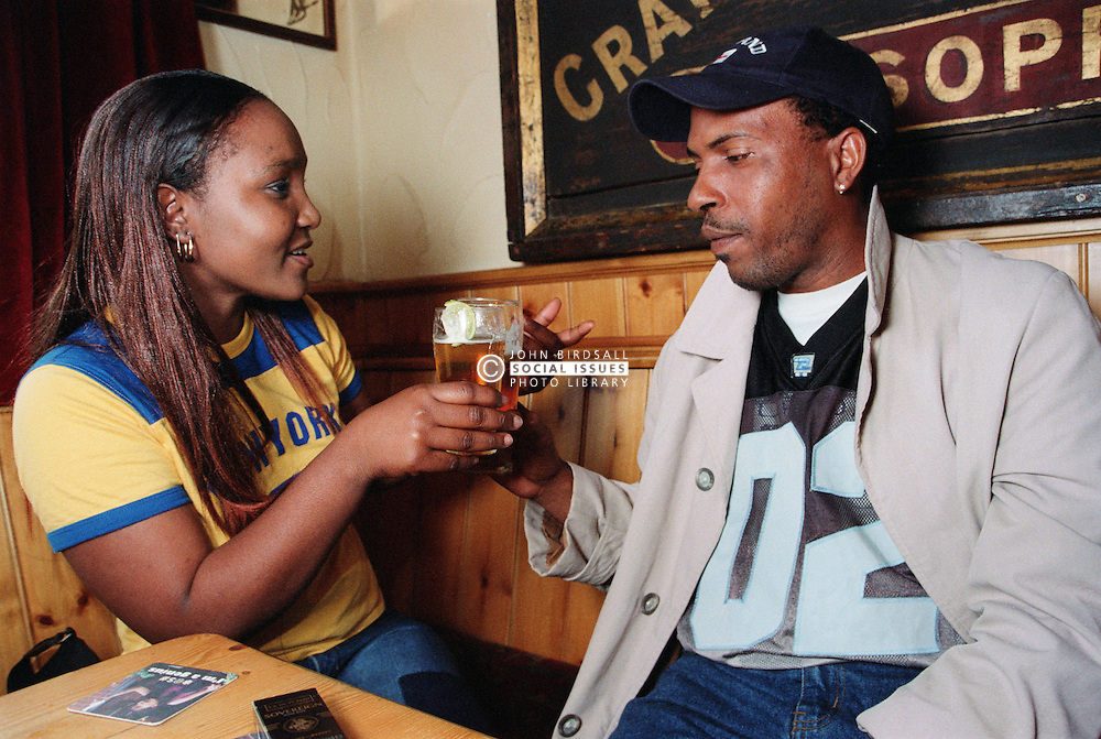 Young man and woman sitting at table in pub drinking pints of beer and talking,