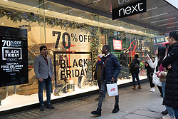 © Licensed to London News Pictures. 23/11/2018. London, UK. Shoppers wait for a Next clothes store to open in Oxford Street at the beginning of Black Friday sales. Photo credit: Ray Tang/LNP
