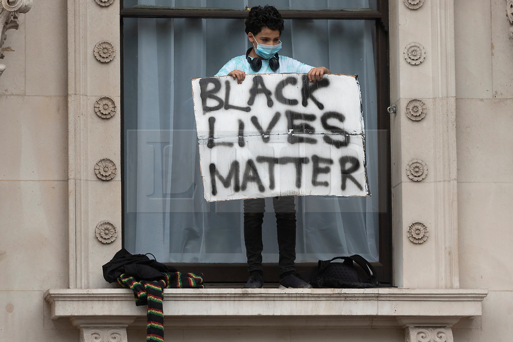 © Licensed to London News Pictures. 03/06/2020. London, UK. A yonng boy holds placard in Whitehall taking part in a demonstration organised by group Black Lives Matter in Hyde Park for the American George Floyd who died whilst being arrested by US policemen Derek Chauvin. His death has caused civil unrest in some US cities. Photo credit: Ray Tang/LNP