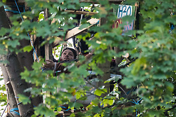Wendover, UK. 10th October, 2021. An activist opposed to the HS2 high-speed rail link is pictured locked into a tree house at Wendover Active Resistance (WAR) camp during the first day of an eviction operation by enforcement agents from the National Eviction Team (NET). WAR camp, which contains tree houses, tunnels, a cage and a 15-metre tower, is currently the largest of the protest camps set up by Stop HS2 activists along HS2's Phase 1 route between London and Birmingham.
