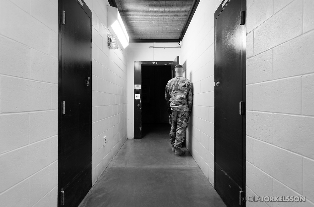 """A military guard at the prison camp at Guantanamo, Cuba, Jan 28 2017, guards a door to an entrance to a cell block.<br /> The guards turn away their faces so you cannot identify them. It is standard operation procedure when pictures are made. When you work as a journalist at the Guantanamo you work under military censorship and all your material is checked every day and approved for publication.<br /> The prison camp on the Guantánamo naval base was the creation of President George W. Bush. The prison camp was considered an important part of the US war on terrorism. Over the years, 779 people have been brought to the camp. 41 people are still detained. Of them, 26 people count as """"forever prisoners"""", indefinite detainees under the Law of War. Two prisoners have been in the camp since it was opened in January 2002. The last prisoner taken to the camp came in March 2008. The so-called war on Terror and the Guantanamo prison camp have been heavily criticized for violation of human rights regarding torture and habeas corpus.<br /> It is unclear what US President Donald Trump wants to do with the camp, but during the election campaign he said that he would fill Guantánamo Bay with """"bad dudes"""". Photo by Ola Torkelsson<br /> Copyright Ola Torkelsson ©"""