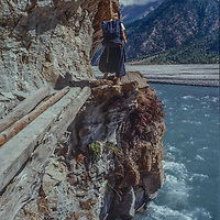 A trekker navigates a catwalk of logs above the Kali Gandaki River, below Mount Annapurna in Nepal.