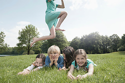Girl jumping over her friends lying on grass in a park, Munich, Bavaria, Germany