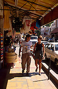 Two tourists walking along sidewalk filled with wares, shopping area, Nogales, Sonora, Mexico..©1990 Edward McCain. All rights reserved. McCain Photography, McCain Creative, Inc.
