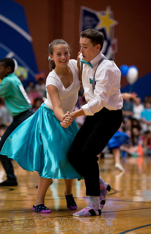 Lucia Casteneda, left, and partner Nathan Williams, both eighth graders, put on their dancing socks during a swing dance competition at Hart Middle School in Pleasanton, Calif., Friday, Oct. 24, 2014. They finished in fourth place. (Photo by D. Ross Cameron)