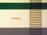 a no smoking stencil on a Washington state ferry is bordered by a broad green band, a gray band, and a band of ventilation louvers