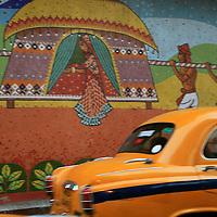 Asia, India, Calcutta. Taxi passes a Mural of Calcutta.