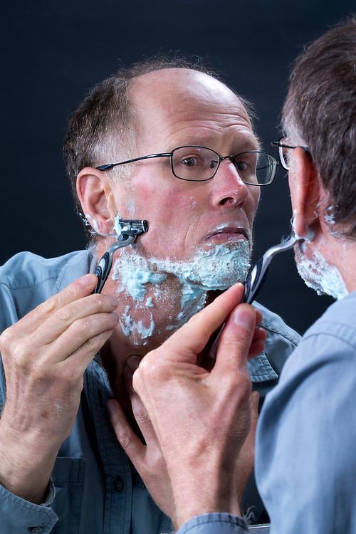 male person shaving his beard