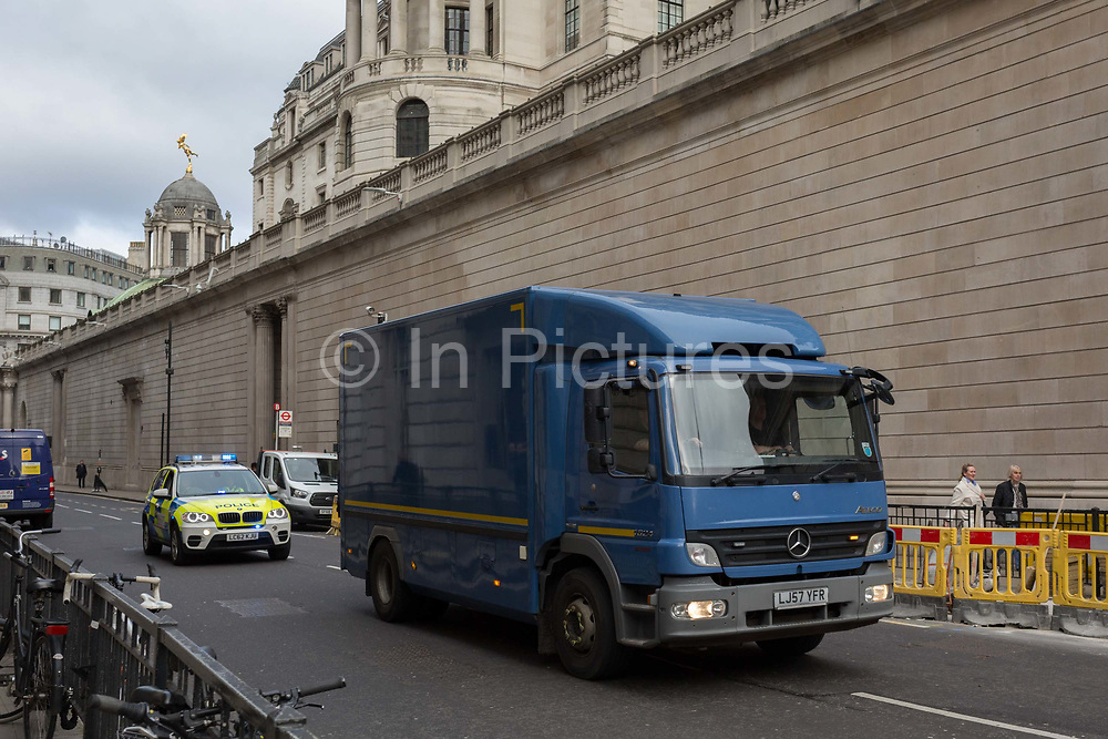 An HGV lorry carrying something inside of high-value often bullion or cash, is driven at speed under police escort, in a convoy on Princes Street and passing beneath the tall walls of the Bank of England, on 4th February 2020, in the City of London, England.