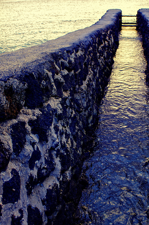 The waterfront at the Waikoloa Resort, Kohala Coast, Hawaii. This mini-dam regulates the ocean's waterflow to and from a man-made pond where fish are bred in a mix of salt and fresh water.